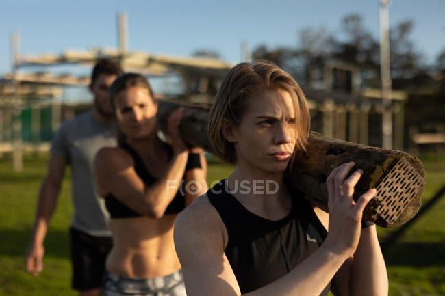 Vue de face de deux jeunes femmes caucasiennes et d'un jeune homme caucasien portant une bûche de bois ensemble sur leurs épaules dans un gymnase extérieur lors d'une séance d'entraînement de bootcamp — Photo de stock