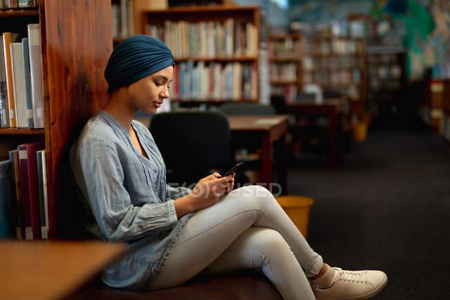 Vue de côté gros plan d'une jeune étudiante asiatique portant un turban à l'aide d'un smartphone dans une bibliothèque — Photo de stock