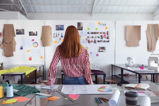Veduta posteriore di una giovane studentessa di moda caucasica che guarda disegni sul muro mentre lavora su un disegno che guarda disegni su un muro in uno studio del college di moda — Foto stock