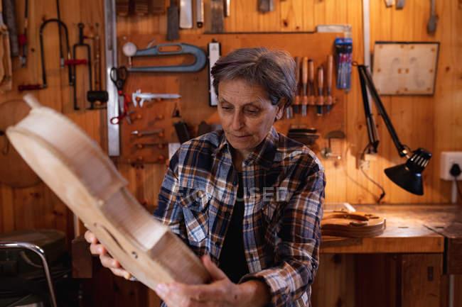 Vista frontal de uma mulher luthier caucasiana sênior segurando o corpo de um violino em sua oficina, com ferramentas penduradas na parede no fundo — Fotografia de Stock