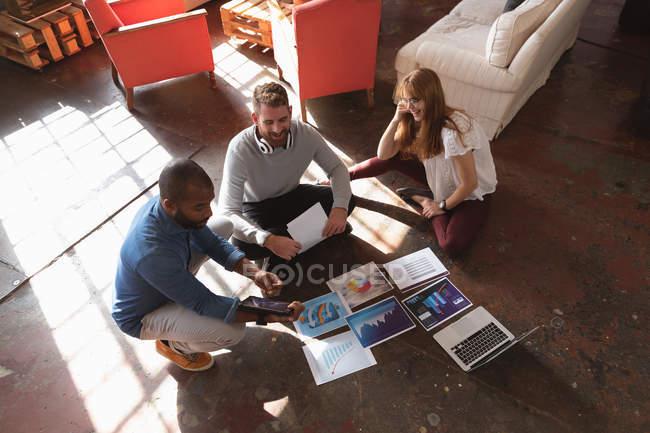 Vue en angle élevé d'un jeune homme afro-américain et d'un jeune homme et femme caucasiens assis sur le sol regardant des visuels ensemble, utilisant un ordinateur portable et parlant tout en faisant du remue-méninges dans un bureau créatif — Photo de stock