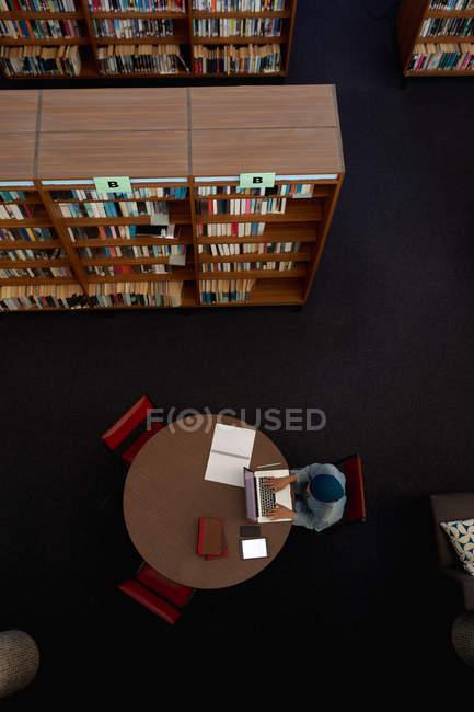 Зверху на молоду азіатську студентку, яка носить тюрбан за допомогою ноутбука і навчається в бібліотеці. — стокове фото
