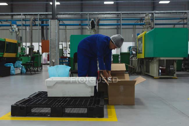 Вид сбоку: молодой афроамериканец, работающий на заводе, упаковывает продукты в коробки для доставки на склад на заводе по переработке — стоковое фото
