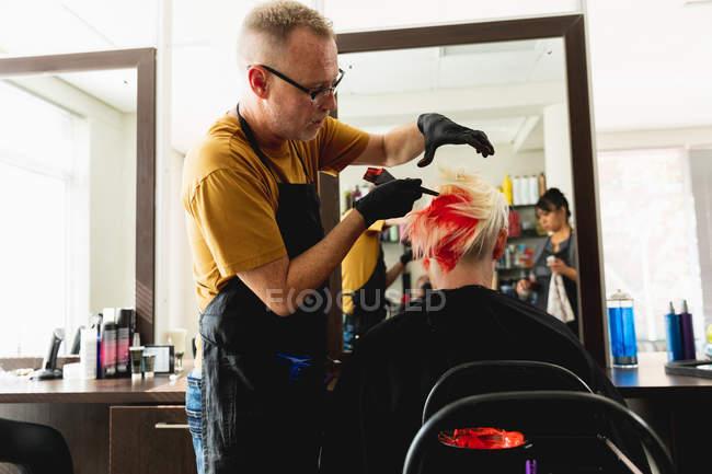 Бічний вид середнього віку Кавказький самець перукаря і молода кавказька жінка з яскраво-червоним волоссям в салоні волосся, з середнім віком змішана раса жіноча перукарня відображена в дзеркалі. — стокове фото