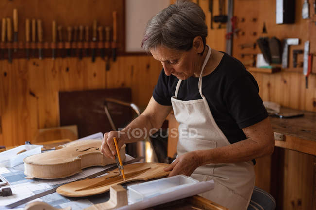 Side view of a senior Caucasian female luthier working on the body of a violin on a workbench in her workshop, with tools hanging up on the wall in the background — Stock Photo