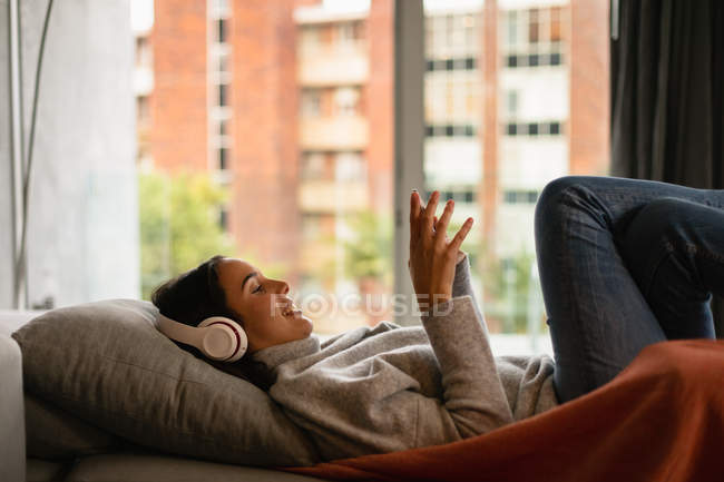 Side view of a smiling young Caucasian brunette woman reclining on a sofa with her legs up, wearing headphones and holding a smartphone — Stock Photo