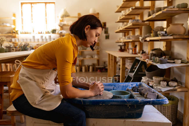 Side view of a young Caucasian female potter sitting and working with clay on a potters wheel in a pottery studio — Stock Photo