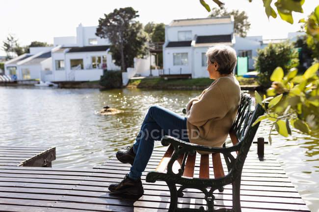 Вид сбоку пожилой кавказки, сидящей на скамейке у озера — стоковое фото