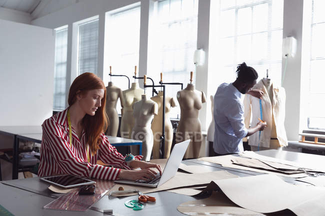 Side view of a young Caucasian female fashion student sitting at a table working on a laptop in a studio at fashion college, with an African American male student working on a jacket design in the background — Stock Photo
