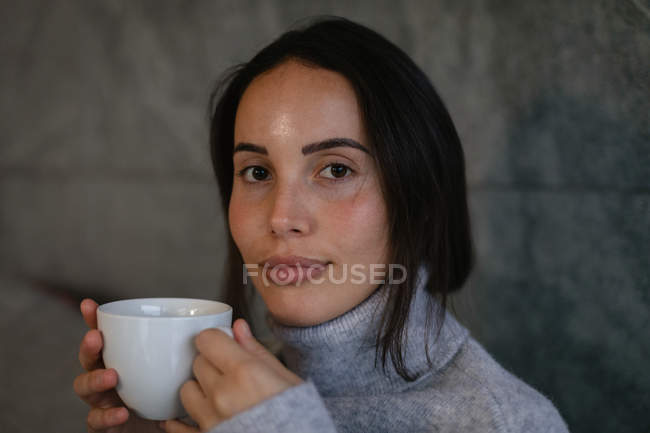 Portrait close up of a young Caucasian brunette woman looking to camera smiling and holding a cup of coffee — Stock Photo