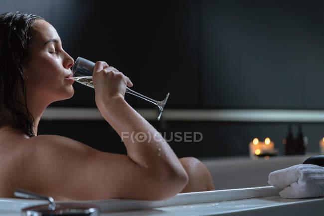 Вид сбоку на молодую брюнетку-кавказку, сидящую в ванной со свечами сбоку и пьющую шампанское с закрытыми глазами — стоковое фото