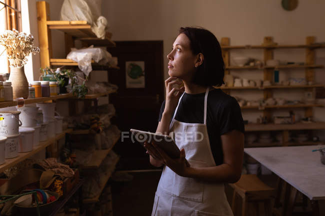 Вид збоку молодий Кавказький жіночий Поттер з її рукою на її підборіддя дивлячись у вікно і за допомогою планшета в гончарні студії — стокове фото