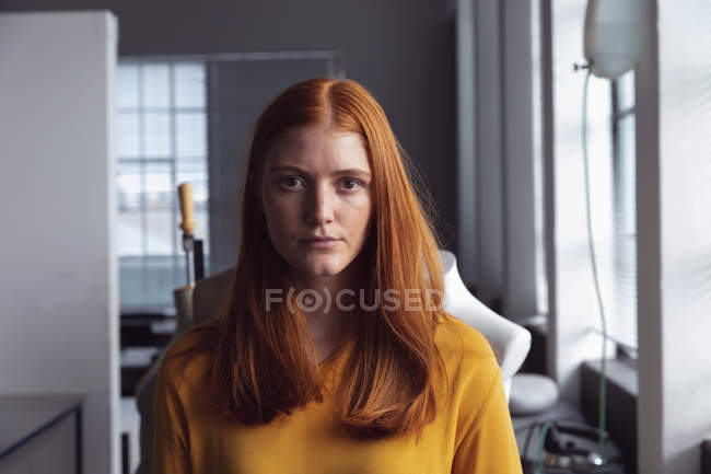 Front view of a young Caucasian female fashion student looking straight to camera in a studio at fashion college — Stock Photo