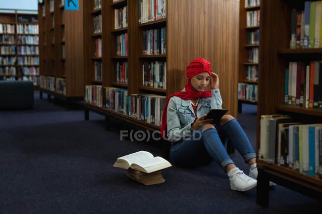 Vista frontale da vicino di una giovane studentessa asiatica che indossa un turbante usando un tablet e studiando in una biblioteca — Foto stock