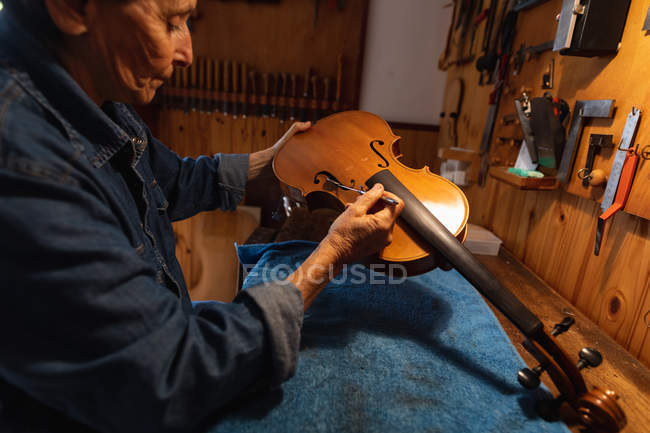 Side view close up of a senior Caucasian female luthier making a violin in her workshop, with tools hanging up on the wall in the background — Stock Photo