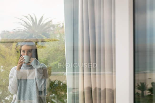 Vista frontale di una giovane donna bruna caucasica con un maglione grigio a collo alto, in piedi su un balcone che beve una tazza di caffè, vista dall'interno, attraverso la finestra — Foto stock