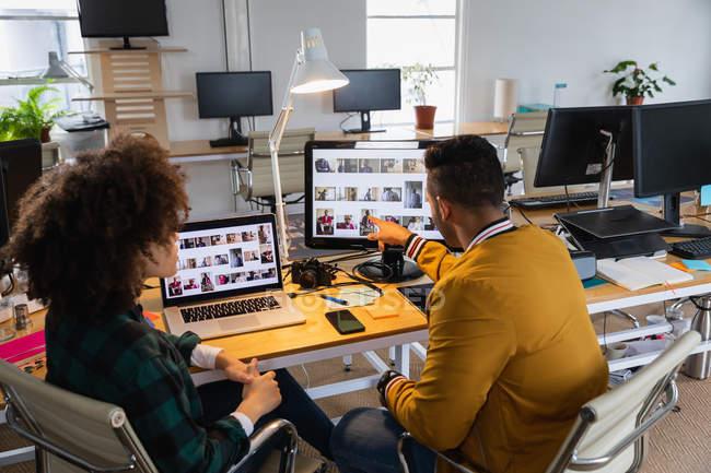 Зворотний бік молодого чоловіка змішаної раси і молодої жінки, яка сидить за столом і дивиться на екран комп'ютера і веде дискусію в творчому кабінеті. — стокове фото