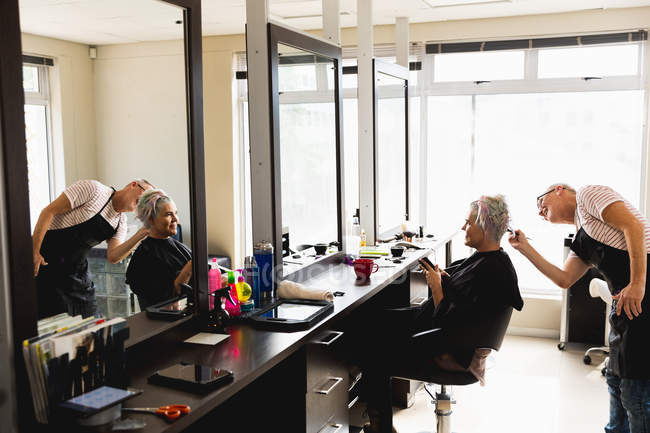Side view of a middle aged Caucasian male hairdresser and a young Caucasian woman having her hair coloured in a hair salon, reflected in a mirror — стокове фото