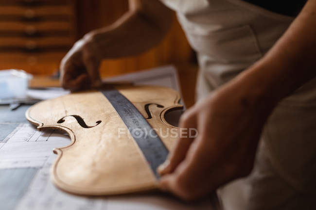 Close up of female luthier measuring the body of a violin on a workbench in her workshop — Stock Photo