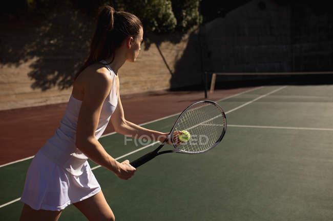 Vista lateral de uma jovem caucasiana jogando tênis em um dia ensolarado, preparando-se para servir com uma parede atrás dela — Fotografia de Stock