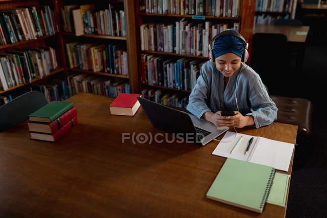 Vista frontale di una giovane studentessa asiatica che indossa turbante e cuffie, utilizzando uno smartphone, un computer portatile e studiando in una biblioteca — Foto stock