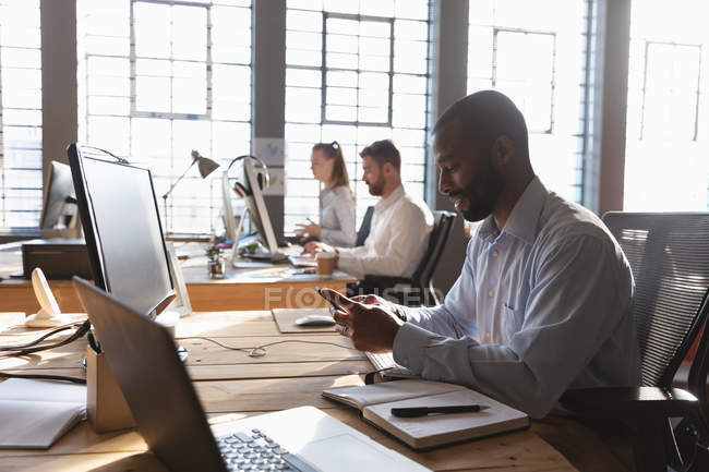 Side view close up of a young African American man sitting at a desk using a smartphone in a creative office, with two colleagues sitting at a desk by a window working in the background — Stock Photo