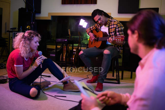 Vista lateral de uma jovem caucasiana sentada no chão cantando com um microfone e um jovem mestiço sentado em um banquinho tocando uma guitarra acústica, enquanto um jovem caucasiano segurando uma caneta e papel escuta em primeiro plano — Fotografia de Stock