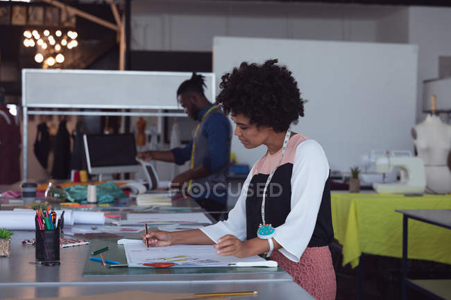 Side view of a young mixed race female fashion student working on a design in a studio at fashion college, with a male student working in the background — Stock Photo