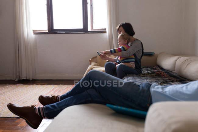 Вид сбоку на молодую кавказскую мать, сидящую на диване и пользующуюся смартфоном со своим ребенком, молодой отец лежит на диване на переднем плане — стоковое фото