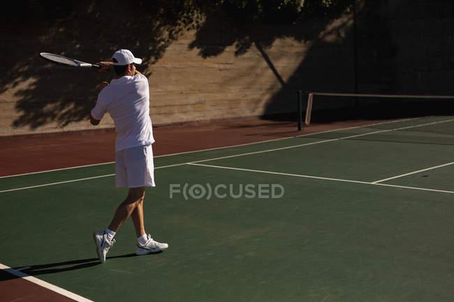 Visão traseira de um jovem caucasiano jogando tênis em um dia ensolarado, retornando uma bola com uma parede atrás dele — Fotografia de Stock