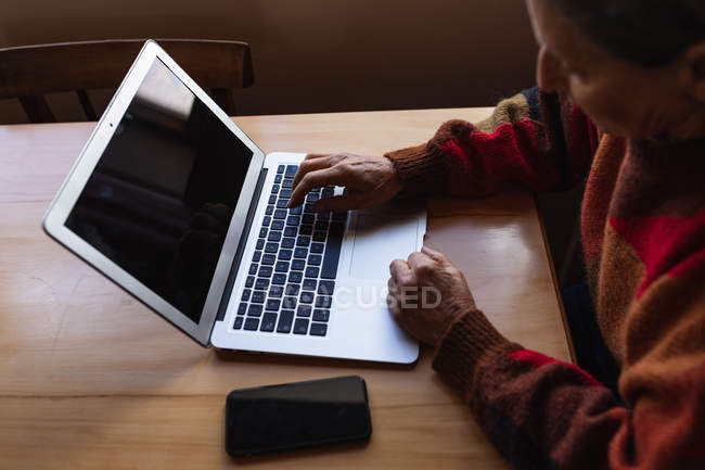 Side view close up of a senior Caucasian woman sitting at a table at home using a laptop computer with a smartphone next to her — Stock Photo