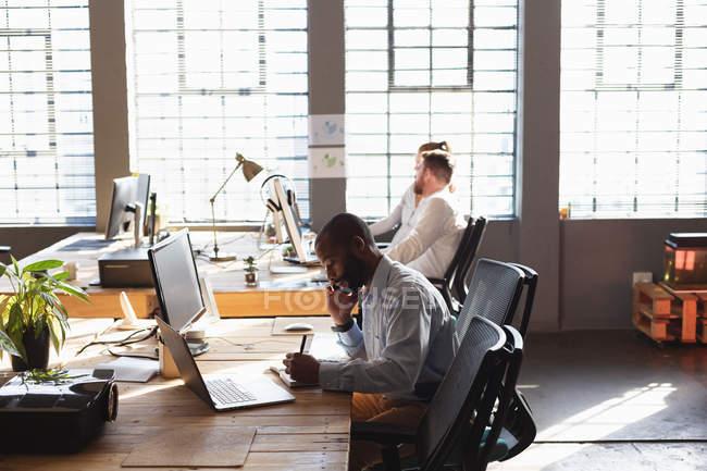 Вид сбоку на молодого афроамериканца, сидящего за столом, разговаривающего на смартфоне и пишущего в креативном кабинете, с двумя коллегами, сидящими за столом у окна на заднем плане — стоковое фото