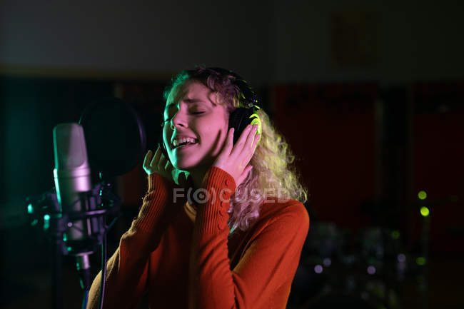 Side view close up of a young Caucasian female singer wearing headphones and singing in front of a microphone in a recording studio, with her eyes closed — Stock Photo