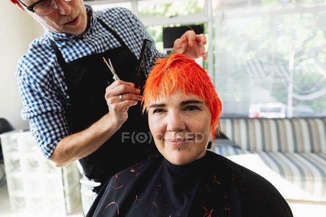 Передня картина, що закриває вигляд середнього віку Кавказького чоловічого перукаря і молодої кавказької жінки, волосся якої яскраво-червоне і стрижене в салоні для волосся. — стокове фото
