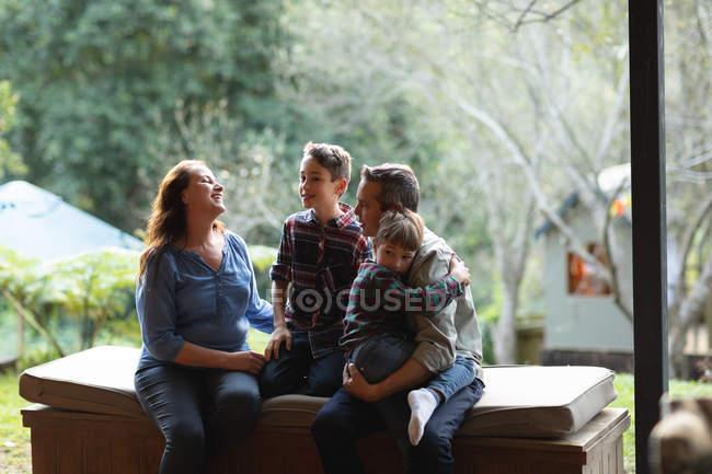 Vista frontal de um homem e mulher caucasiano de meia-idade abraçando com seus dois filhos pré-adolescentes em casa — Fotografia de Stock
