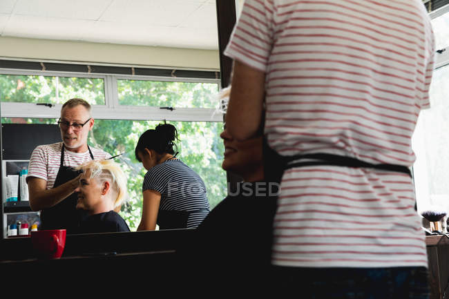 Side view close up of a middle aged Caucasian male hairdresser and a young Caucasian woman having her hair styled in a hair salon, with a middle aged mixed race female hairdresser reflected in a mirror — стокове фото