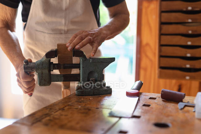 Front view close up of female luthier using a vice attached to a workbench in her workshop, with chest of drawers in the background — Stock Photo