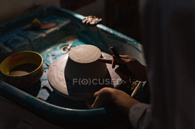 Side view mid section of female potter using a tool to shape the base of a bowl on a potters wheel in a pottery studio — Stock Photo