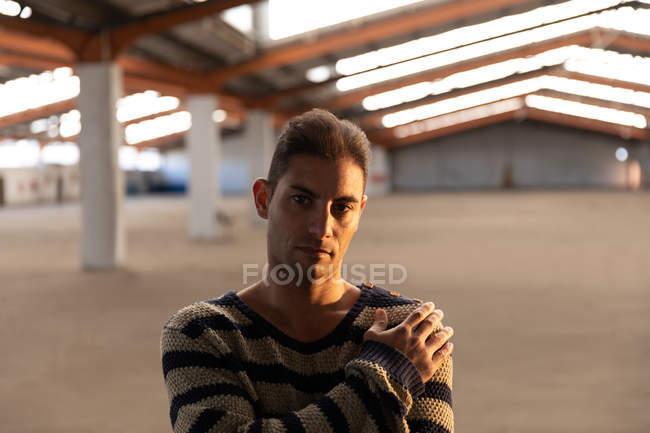 Ritratto di un giovane uomo in piedi con la mano sulla spalla, che guarda la telecamera in una stanza vuota in un magazzino abbandonato — Foto stock