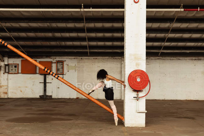 Side view of a young mixed race female ballet dancer wearing pointe shoes dancing standing on one leg on her toes the other leg raised on a structural pole in an empty room at an abandoned warehouse — Stock Photo