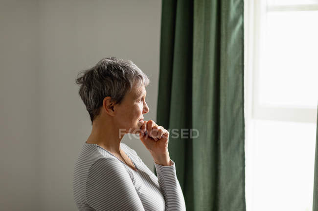 Вид сбоку зрелой кавказской женщины с короткими седыми волосами, стоящей и смотряй из окна дома — стоковое фото
