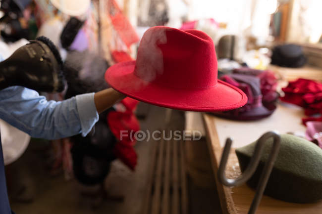 Close up of the hand of a woman holding a red hat while she operates a machine to steam clean it in the workshop at a hat factory, other hats visible in the background — Stock Photo