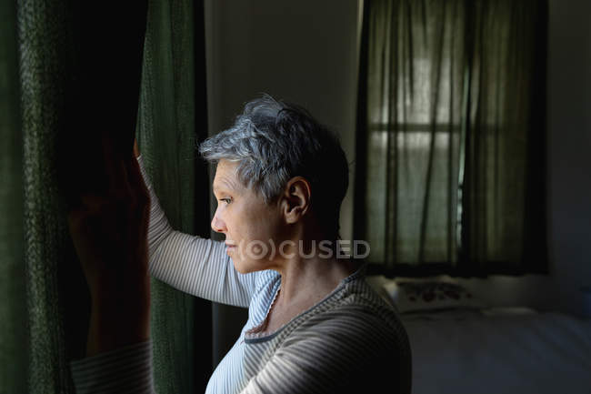 Side view close up of a mature Caucasian woman with short grey hair drawing the curtains and looking out of the window at home — Stock Photo