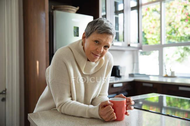 Porträt einer reifen kaukasischen Frau mit kurzen grauen Haaren, die in ihrer Küche sitzt, eine Tasse Kaffee hält und in die Kamera lächelt — Stockfoto