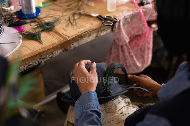 Over the shoulder view of woman holding and adding the finishing touches to a hat in the workshop at a hat factory, with a work table and materials in the background — Stock Photo