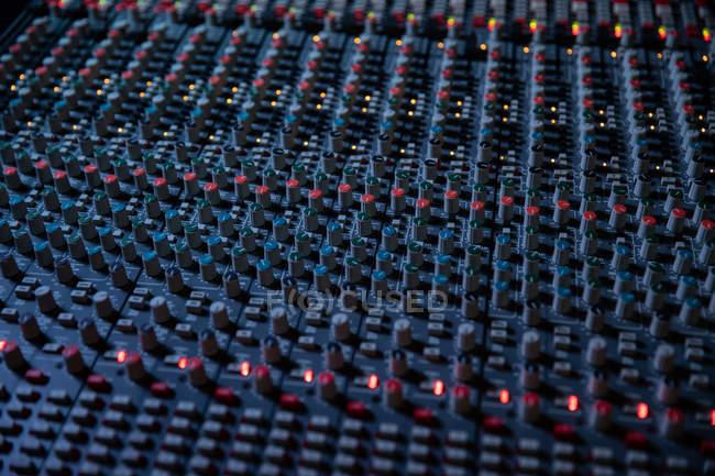 Botões, botões e luzes dos comandos do canal numa mesa de mistura multipista num estúdio de gravação — Fotografia de Stock