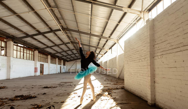 Side view of a young mixed race female ballet dancer wearing a blue tutu and pointe shoes dancing on her toes in shaft of sunlight in an empty room at an abandoned warehouse — Stock Photo