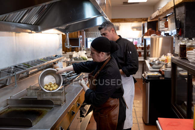 Side view close up of a middle aged Caucasian male chef overseeing the work of a young Caucasian female chef, draining potatoes in a restaurant kitchen — Stock Photo