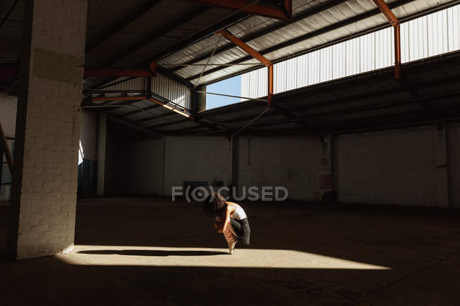 Side view of a young mixed race female ballet dancer wearing pointe shoes squatting down balanced on her toes in shaft of sunlight while dancing in an empty room at an abandoned warehouse — Stock Photo