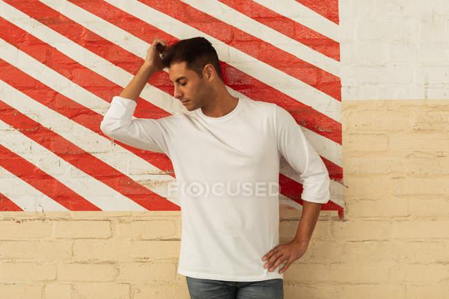Вид спереду молодої людини, що схиляється проти стіни, дряпає голову, яка Обернена збоку, а з рук на стегні в порожньому приміщенні з перетином червоної і білої смугастої стіни на занедбаному складі — стокове фото
